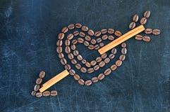 Coeur avec la flèche de cupidon faite de grains de café sur un fond foncé Image stock