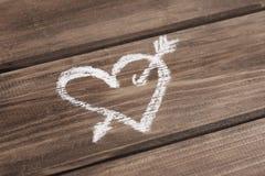 Coeur avec la flèche dessinée avec la craie sur le fond en bois Photo libre de droits