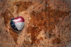 Coeur avec le drapeau d'état de la Caroline du Nord sur un fond de papier de fente de carte du monde de vintage Image libre de droits