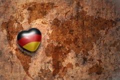 Coeur avec le drapeau national de l'Allemagne sur un fond de papier de fente de carte du monde de vintage Photo libre de droits