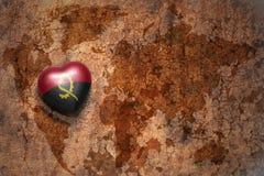 Coeur avec le drapeau national de l'Angola sur un fond de papier de fente de carte du monde de vintage Image libre de droits