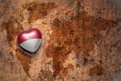 Coeur avec le drapeau national de l'Indonésie sur un fond de papier de fente de carte du monde de vintage Photo libre de droits