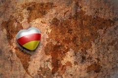 Coeur avec le drapeau national de l'Ossétie-du-Sud sur un fond de papier de fente de carte du monde de vintage Photos stock