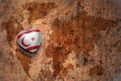 Coeur avec le drapeau national de la Chypre du nord sur un fond de papier de fente de carte du monde de vintage Photo libre de droits