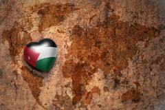 Coeur avec le drapeau national de la Jordanie sur un fond de papier de fente de carte du monde de vintage Photographie stock libre de droits