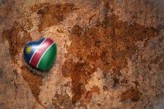 Coeur avec le drapeau national de la Namibie sur un fond de papier de fente de carte du monde de vintage Photo libre de droits