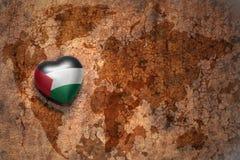 Coeur avec le drapeau national de la Palestine sur un fond de papier de fente de carte du monde de vintage Photo stock