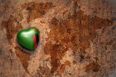 Coeur avec le drapeau national de la Zambie sur un fond de papier de fente de carte du monde de vintage Image stock
