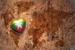 Coeur avec le drapeau national de myanmar sur un fond de papier de fente de carte du monde de vintage Photographie stock