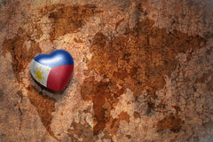 Coeur avec le drapeau national de Philippines sur un fond de papier de fente de carte du monde de vintage Image stock
