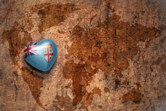 Coeur avec le drapeau national des Fidji sur un fond de papier de fente de carte du monde de vintage Photos libres de droits