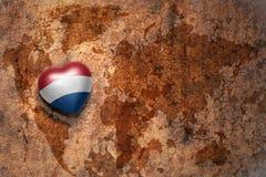 Coeur avec le drapeau national des Hollandes sur un fond de papier de fente de carte du monde de vintage Photos libres de droits