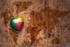 Coeur avec le drapeau national du Bénin sur un fond de papier de fente de carte du monde de vintage Photographie stock libre de droits