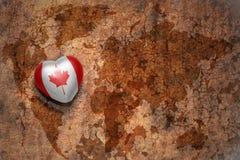 Coeur avec le drapeau national du Canada sur un fond de papier de fente de carte du monde de vintage Photographie stock