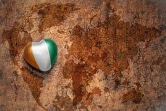 Coeur avec le drapeau national du divoire de petite ferme sur un fond de papier de fente de carte du monde de vintage Image libre de droits