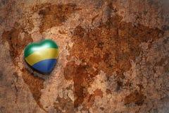 Coeur avec le drapeau national du Gabon sur un fond de papier de fente de carte du monde de vintage Images libres de droits