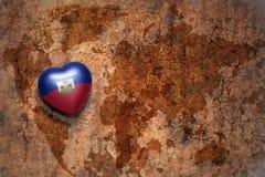 Coeur avec le drapeau national du Haïti sur un fond de papier de fente de carte du monde de vintage Photographie stock