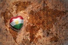 Coeur avec le drapeau national du Kurdistan sur un fond de papier de fente de carte du monde de vintage Image libre de droits