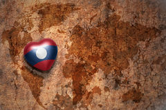 Coeur avec le drapeau national du Laos sur un fond de papier de fente de carte du monde de vintage Image stock