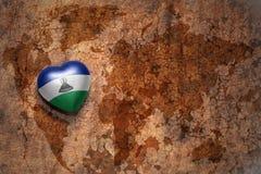 Coeur avec le drapeau national du Lesotho sur un fond de papier de fente de carte du monde de vintage Photographie stock libre de droits