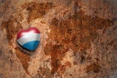 Coeur avec le drapeau national du Luxembourg sur un fond de papier de fente de carte du monde de vintage Photos libres de droits