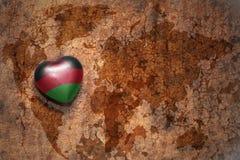 Coeur avec le drapeau national du Malawi sur un fond de papier de fente de carte du monde de vintage Photos libres de droits