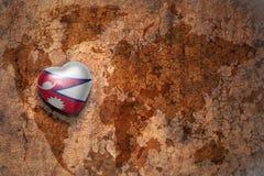 Coeur avec le drapeau national du Népal sur un fond de papier de fente de carte du monde de vintage Images stock