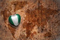 Coeur avec le drapeau national du Nigéria sur un fond de papier de fente de carte du monde de vintage Image stock