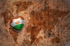 Coeur avec le drapeau national du Niger sur un fond de papier de fente de carte du monde de vintage Images libres de droits