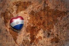 Coeur avec le drapeau national du Paraguay sur un fond de papier de fente de carte du monde de vintage Image libre de droits