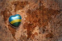 Coeur avec le drapeau national du Rwanda sur un fond de papier de fente de carte du monde de vintage Photo libre de droits