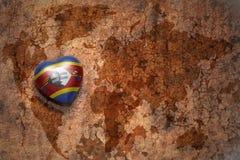 Coeur avec le drapeau national du Souaziland sur un fond de papier de fente de carte du monde de vintage Images stock