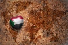 Coeur avec le drapeau national du Soudan sur un fond de papier de fente de carte du monde de vintage Photo stock
