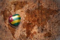 Coeur avec le drapeau national du Togo sur un fond de papier de fente de carte du monde de vintage Image stock
