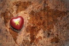 Coeur avec le drapeau national du Vietnam sur un fond de papier de fente de carte du monde de vintage Image libre de droits