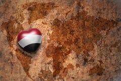 Coeur avec le drapeau national du Yémen sur un fond de papier de fente de carte du monde de vintage Photo stock