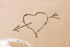 Coeur avec une flèche écrite sur le sable Image libre de droits