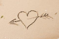 Coeur avec une flèche écrite sur le sable Photos libres de droits