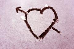 Coeur avec une flèche dessinée sur la neige Rose modifié la tonalité Photo libre de droits