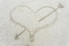 Coeur avec une flèche dessinée sur le sable Photographie stock libre de droits