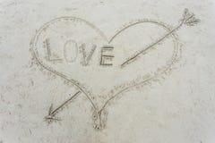 Coeur avec une flèche dessinée sur le sable Photographie stock