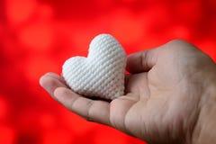 Coeur blanc à disposition avec le fond rouge Photos libres de droits