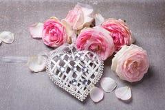 Coeur blanc décoratif et roses roses Photo stock