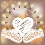 Coeur blanc de hachure et mitaines tricotées sur le fond brouillé avec la guirlande ronde de lumières Photos libres de droits