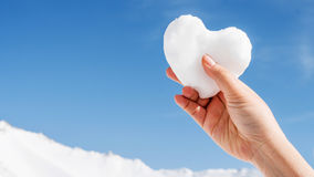 Coeur blanc de neige à disposition sur la montagne Images stock