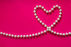Coeur blanc de perle sur un fond rose lumineux Perles de perle en Th Photographie stock libre de droits