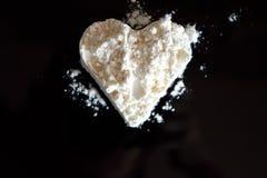 Coeur blanc de poudre sur le fond brillant noir Images libres de droits