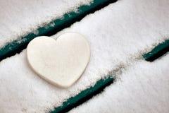 Coeur blanc sur le banc couvert de neige Rose rouge photographie stock