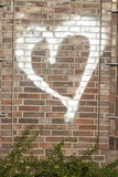 Coeur blanc sur un mur de briques Photo libre de droits