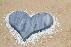 Coeur bleu dans le sable. Photo stock